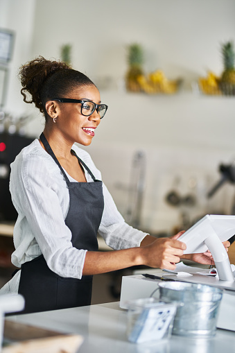 friendly african american shop assistant using pos terminal to input orders at restaurant 1141491870