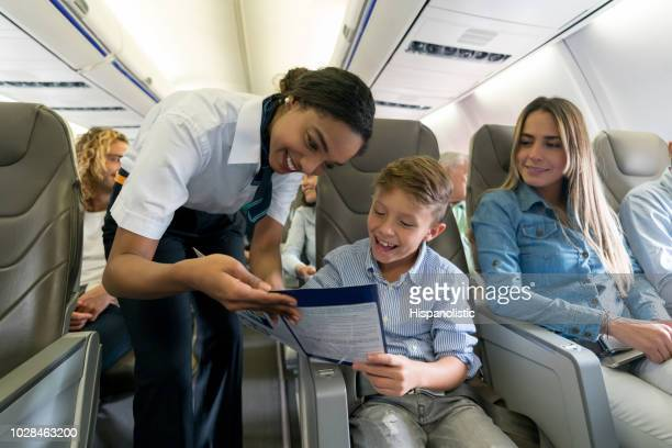 friendly air hostess helping a boy in an airplane - crew stock pictures, royalty-free photos & images