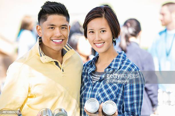 Friendly Asian couple volunteering together at donation food drive