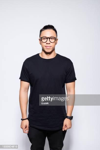 jovem asiático amigável em roupas pretas - izusek - fotografias e filmes do acervo