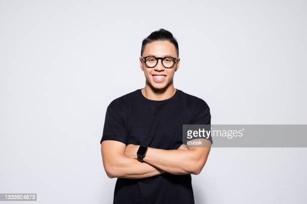 friendly asian young man in black clothes - izusek stock pictures, royalty-free photos & images