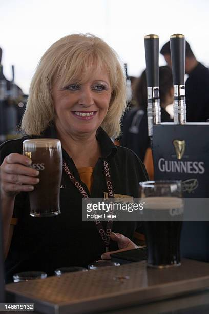 friendly bartender pouring pint of guinness in gravity bar at guinness storehouse brewery. - guinness stock pictures, royalty-free photos & images