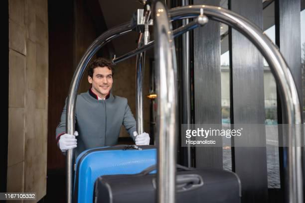 チェックアウト後にカートでゲストの荷物を移動するフレンドリーなベルホップ - ホテルマン ストックフォトと画像