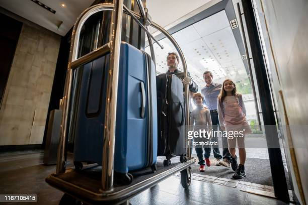 friendly bellhop pushing cart with guest family luggage on cart ready to check in into hotel - hotel stock pictures, royalty-free photos & images