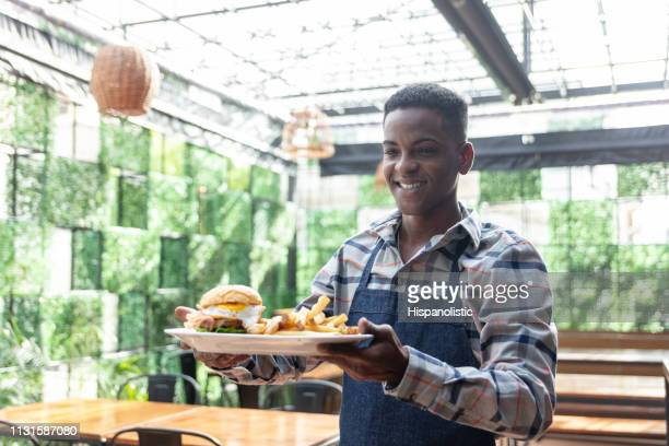 friendly black male waiter taking an order of burger and fries to customer at restaurant - hispanolistic stock photos and pictures