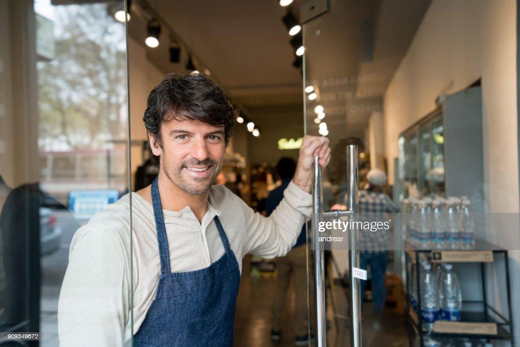 Dono de negócio amigável abrir a porta de seu mercado sorrindo : Foto de stock