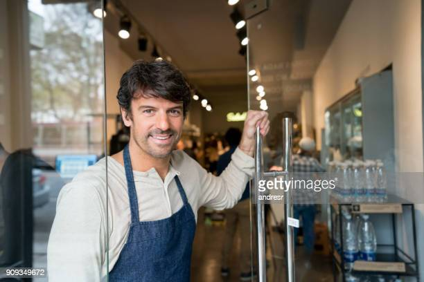 friendly business owner opening the door of his market smiling - happy merchant stock pictures, royalty-free photos & images