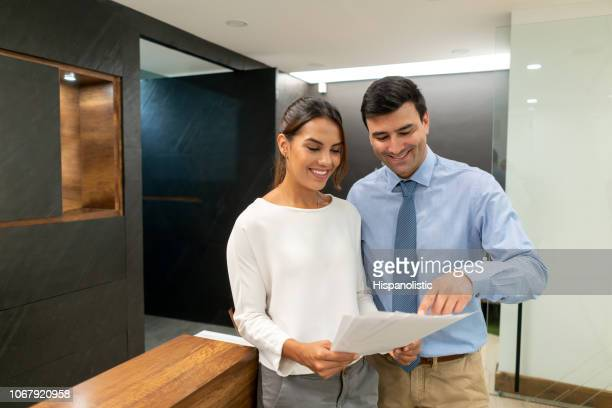 friendly business partners checking some documents and man pointing at something both smiling - hispanolistic stock photos and pictures