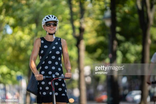 friendly businesswoman with cycling helmet on electric push scooter in city - medium shot stock pictures, royalty-free photos & images
