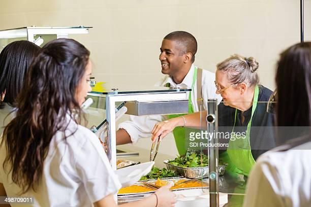 Friendly cafeteria workers serving hot meal to high school students