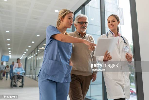 friendly doctor and nurse talking to senior patient at the hospital while showing some documents - civilian stock pictures, royalty-free photos & images
