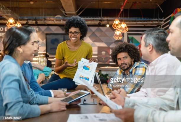 gerente preto fêmea amigável que mostra sua equipe informação nos originais que olham muito felizes - liquidação evento comercial - fotografias e filmes do acervo