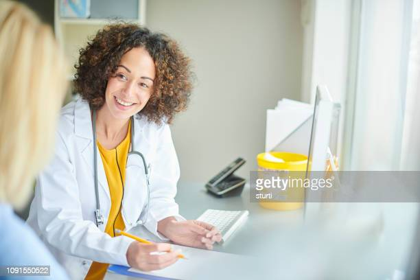 friendly female gp with patient - doctor's surgery stock pictures, royalty-free photos & images