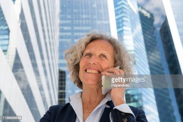 Friendly female senior on a phone call at a business district smiling