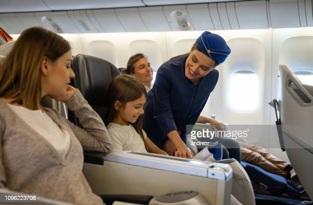 friendly flight attendant helping a girl in an airplane - crew stock pictures, royalty-free photos & images
