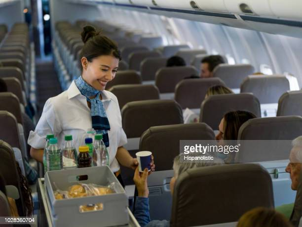 friendly flight attendant serving drinks in an airplane - flight attendant stock pictures, royalty-free photos & images