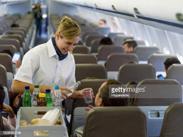 friendly flight attendant serving drinks in an airplane - crew stock pictures, royalty-free photos & images