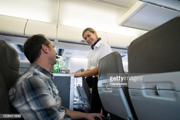 Freundlichen Stewardess serviert Getränke im Flugzeug