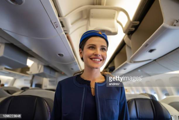 friendly flight attendant smiling on the aisle in an airplane - crew stock pictures, royalty-free photos & images