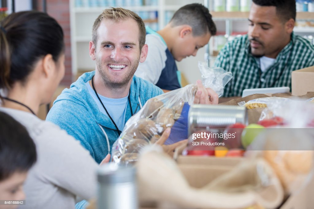 Friendly food bank volunteer accepts donations : Stock Photo