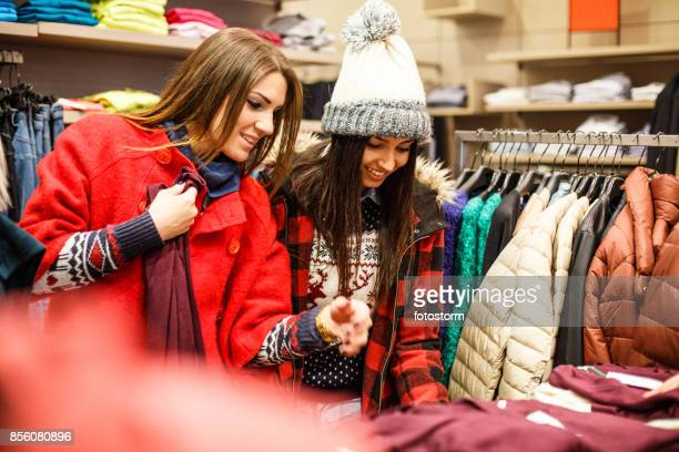 friendly girls during their enjoyable shopping - multi colored coat stock photos and pictures