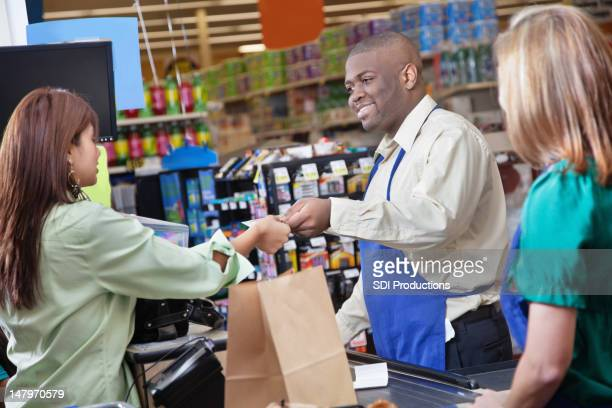 Friendly grocery store clerk giving change to customer