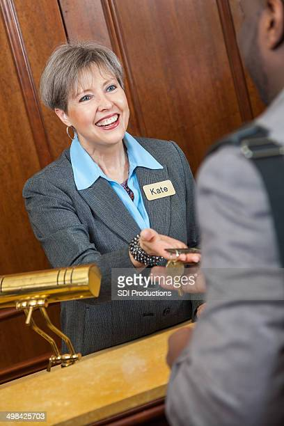 Friendly hotel manager or clerk giving room key to guest
