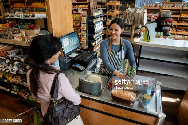 friendly latin american cashier helping female customer check out passing the products through the bar code reader - checkout stock pictures, royalty-free photos & images