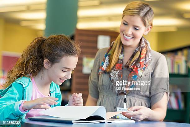 Friendly librarian helping elmentary age girl read book in library