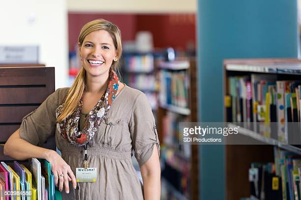 Friendly librarian smiling in children's section of public library