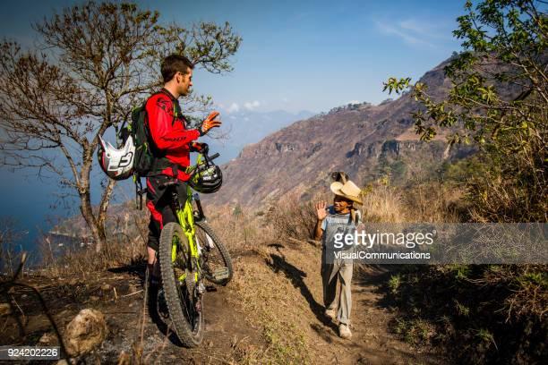 Friendly local Mayan man talking to bike rider visiting Lake Atitlan.