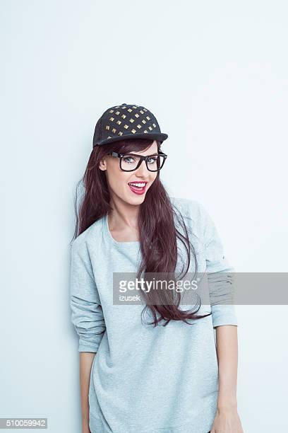 Friendly long hair brunette wearing nerd glasses and baseball cap