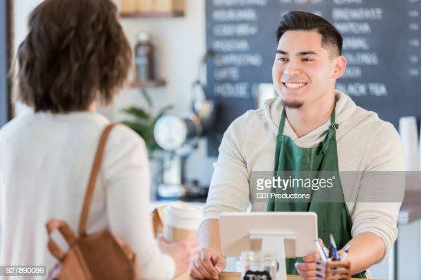 friendly male barista helps female customer - service occupation stock pictures, royalty-free photos & images