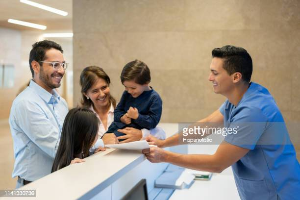 friendly male nurse handing a form to fill in to beautiful single father with his kids and grandmother at the hospital - medical receptionist uniforms stock pictures, royalty-free photos & images