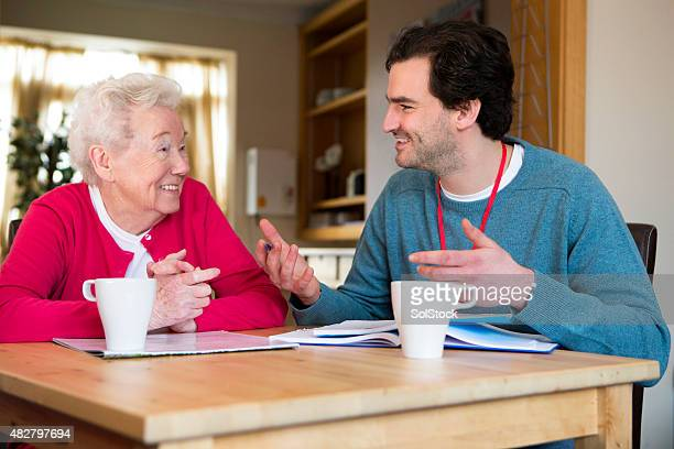 Friendly male volunteer assisting a senior woman with paperwork.
