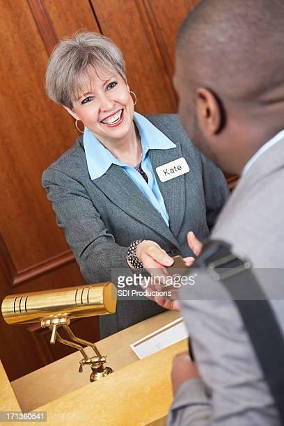 Gestionnaire souriant et sympathique aide les clients à l'hôtel de nice