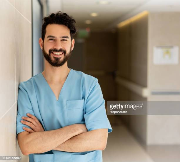 friendly medical resident at the hospital leaning against the wall with arms crossed smiling at camera - civilian stock pictures, royalty-free photos & images