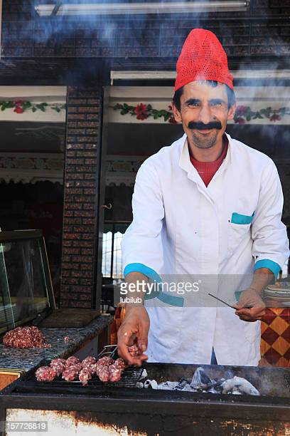 Friendly Moroccan man doing the barbeque ready for kebab