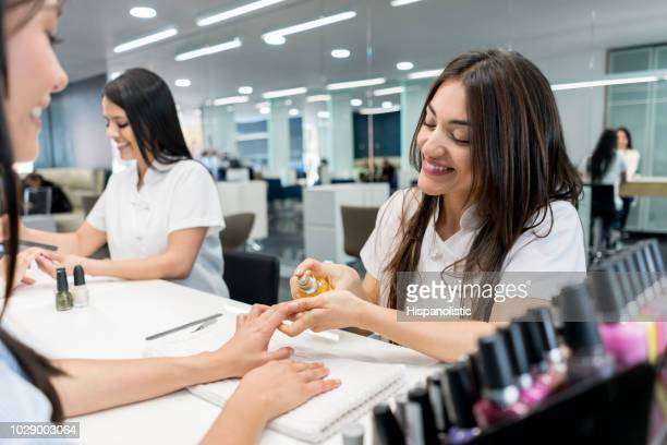 friendly nail technician applying a product on customers hands - fingernail stock pictures, royalty-free photos & images