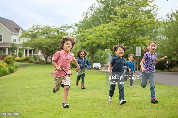 friendly neighborhood children playing together outside - kids playing tag stock photos and pictures