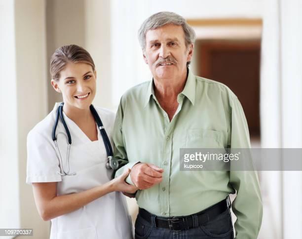 Friendly nurse assisting a senior man to walk in hospital