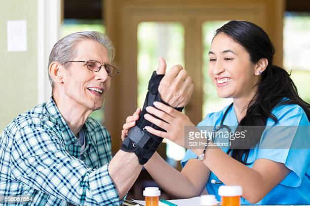 friendly nurse examines senior patient's wrist - brace stock pictures, royalty-free photos & images
