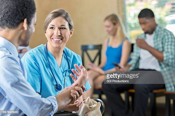 friendly nurse examining patient in hospital triage center - emergency medicine stock pictures, royalty-free photos & images