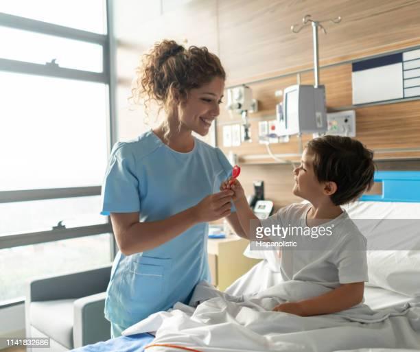 infirmière amicale donnant une sucette à doux petit garçon s'asseyant sur le lit d'hôpital les deux souriant - repas servi photos et images de collection