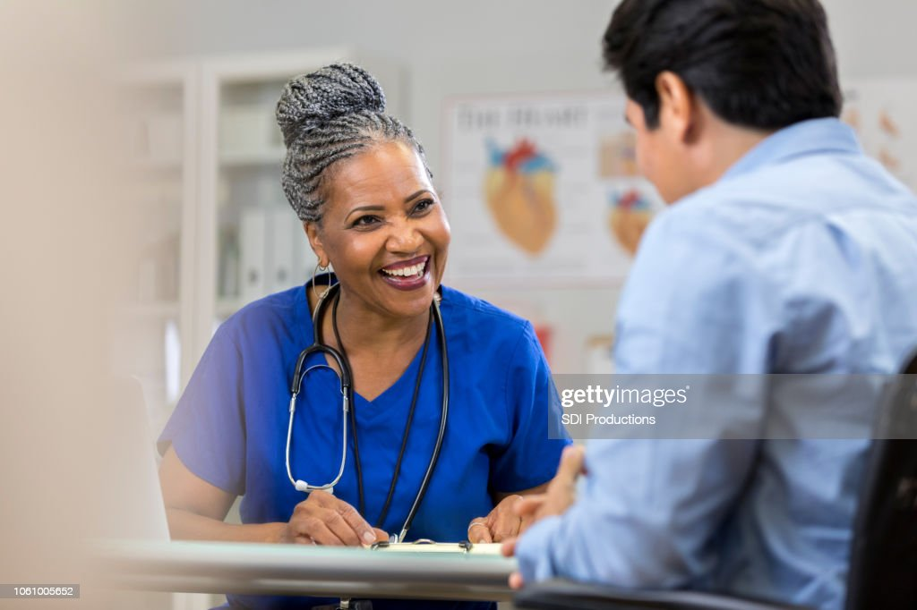 Friendly nurse laughs with patient : Stock Photo