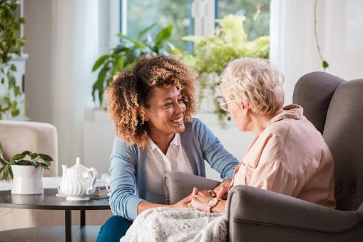 Friendly nurse supporting an eldery lady 1092112802