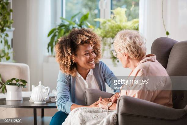 friendly nurse supporting an eldery lady - social issues stock pictures, royalty-free photos & images