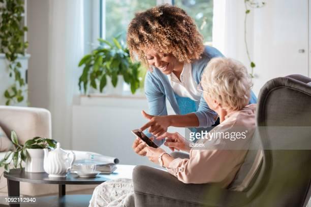 amigável enfermeira apoio de mulher sênior - assistente social - fotografias e filmes do acervo