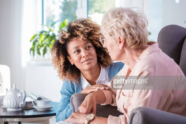 friendly nurse taking care of eldery lady - alzheimer's disease stock pictures, royalty-free photos & images