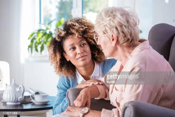 Friendly nurse taking care of eldery lady